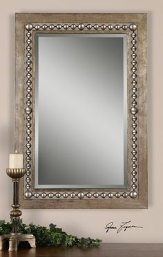 "Fidda  Item #13724  Frame is made of hand forged metal finished in antiqued silver leaf with black undertones. Features an open design around the bead details to allow wall color to show thru. Mirror has a generous 1 1/4"" bevel. May be hung horizontal or vertical.  Designer:	Grace Feyock  Dimensions:	33 W X 49 H X 2 D (in)  Weight (lbs):	48  UPC Number:	792977137246"