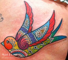 Full colour thigh tattoo of a brightly coloured traditional style swallow with henna style pattern work inside it.