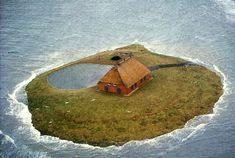 Hallig Habel, a farm in the flatlands of North Frisian Islands, Germany, during an extreme high tide. Handbuilt Shelter by Lloyd Kahn