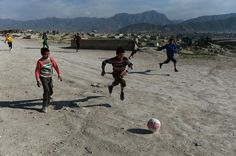 Afghan children play football near a cemetery on a hilltop in Kabul on April 12, 2014.