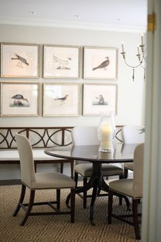 The colors and beautiful gallery wall of bird paintings bring a natural touch to this new traditional dining room without the introduction of rustic elements