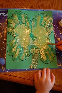 Handprint Shamrock : we did green paint handprints on white paper and then sprinkled with green glitter.  Looked so cute and was very striking on the bulletin board.