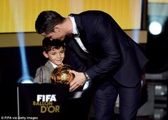 Ronaldo - pictured with his son  - receives the Ballon d'Or award on Monday night...