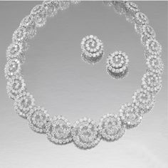 DIAMOND DEMI-PARURE: The necklace designed as an articulated series of interlocking spiral motifs, length approximately 370mm,  together with a pair of ear clips en suite, collapsible clip and post fittings, British hallmarks for London, 2006, case, French assay marks.
