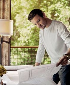 Jeremy With Beard and Mustache Wearing a White Long-Sleeved T-Shirt and Black Pants Looking at Blueprints and Standing in Front of a Large Picture Window for the Robb Report Home & Style Magazine Shoot - May 2016 Issue