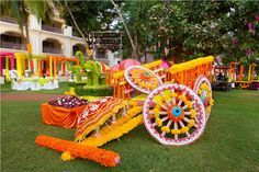A bullock cart, beautifully decorated with marigold flowers with colorful umbrellas placed around, used as decor prop at a Mehendi setup!