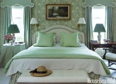 """To replace the master bedroom's shutters, Redd had custom curtains and pelmets made in pea-green silk taffeta with cream trim """"for drama and luxury."""" The carpet is from Stark. """"Every bedroom needs a note of softness,"""" he says."""
