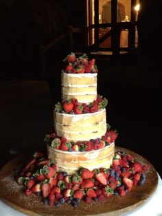 Naked wedding cake. Filled with rhubarb & vanilla bean jam & iced with buttercream. Decorated with fresh local strawberries & berries.