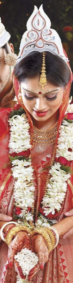 "Bengali bride with traditional sholapith plant stem/bark crafted tiara called ""mukut"" meaning - crown, and fresh Rajanigandha and rose garland. Sholapith stem/bark has a cork like spongy texture and can be crafted with fine designs."