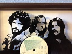 """The Eagles """"Hotel California"""" hand cut framed vinyl LP record art collectible gift  This is an image of The Eagles hand-cut from their LP album """"Hotel California"""". It is mounted in front of (raised above) a white background for enhanced visibility and is framed. The album's front cover is displayed behind the frame…"""