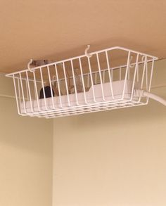 Screw hooks under a desk to hang a shower basket and keep plugs & leads off the floor