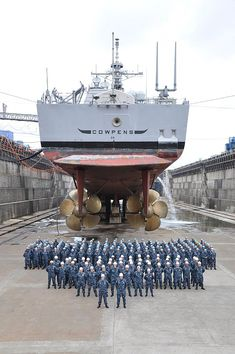 YOKOSUKA, Japan (July 6, 2010) The officers and crew of the guided-missile cruiser USS Cowpens (CG 63) pose for a group photo under the ship at Fleet Activities Yokosukas dry dock six.
