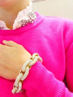JCrew cashmere bright pink sweater, white ruffle button up, and chunky gold link bracelet