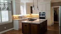 White kitchen cabinets with marble top island by Woodmaster Woodworks