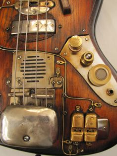 """tonycochranguitars:  Ask & ye shall receive … Sparkycaster Bass Steampunk Guitar unveiled!Detail pics link and Like us at www.facebook.com/TonyCochranGuitarsDarren Thompson contracted so violently when he was electrocuted at San Cornelius prison, in 1967, that the arms of the chair broke. The pieces were used by William Muldover to repair an old bass electric guitar he played in the prison church ensemble """"The Caged Angels"""" … Might explain the odd, but pleasant, tone."""