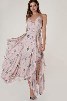 Sleeveless printed maxi dress with chic sharkbite hem. Classic V-neckline with adjustable shoulder straps that criss crosses in back. Floral patterns throughout with smooth lining and hidden back zip closure.