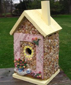 "Chantilly Lace and Roses Cedar birdhouse with stones and river rock collected from the shores of Lake Michigan, local rivers and from creek beds and recycled embellishments. Roof and base is weatherproof stain in Eggnog Yellow. Suitable for outdoor or indoor décor. Removable base for easy clean out.   13"" high X 7"" wide X 6"" deep       1 1/4"" opening      $60.00 plus shipping"
