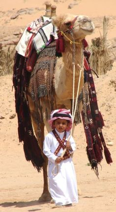 Child with arabian camel in the desert