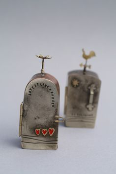 Bronwen Tyler-Jones: mini metal box amulets. Like the door handle on the back one.