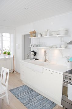 Kitchen idea #9 - I love the blue accent the rug gives to an otherwise very white space.