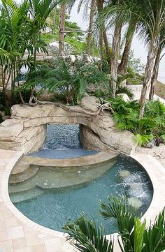 This fabulous waterfall pool with bar stools is the perfect refreshing spot for an cozy tropical feel. #greatoutdoorpools #waterfronthomes #FRLM