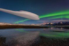 Nordlichter und Wolken kreuzen sich über der Gletscherlagune