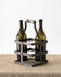 Portabottiglie in ferro dotato di manico in legno con tracce di vernice originale. Dal design semplicissimo, la variante principale sta nel numero dei comparti. Quelli che potevano accomodare quattro bottiglie erano solitamente destinate al trasporto di latte, mentre quelli a sei o più comparti erano usate per le bottiglie di vino. Dimensioni: 20 x 20 x 36 cm