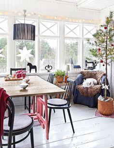 Vanhasta hirsirungosta koottu talo sai uuden pikkuruutuisen lasikuistin.  Valkoinen huone on valoisa ruokailutila. Joulumänty tuo iloista  tunnelmaa. Katso ihana kuva!