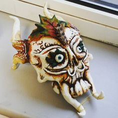 I finished this today! Bases on a project on Dan masks mine has influences from all over the world and i like making scary things. Bit of day of the dead bit of green man various African tribal influences and a real life feather. Made of air dry clay and painted with acrylic and ink. #art #sculpture #scary #spookyscaryskelletons #horns #fangs #demon #masks #dayofthedead #greenman #leaf #leafy #leaves #skull #scaryskull #eyeballs #clay #ceramics #illustration #artstudent by emily.rose_carter