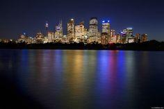 Vista nocturna da baía de Sydney. Esta baía é um porto natural em volta do qual se situa a maior aglomeração urbana da Austrália, a cidade de Sydney.