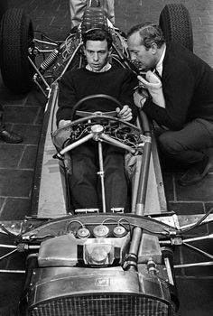 Jim Clark and Colin Chapman.. Jim surrounded by fuel tanks