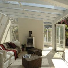 Garden room with bi-folding doors, white stone floor and wood-burning stove