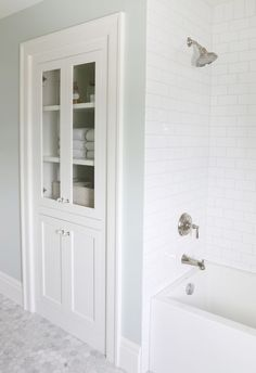 built-in linen closet, marble, subway tile with gray grout.