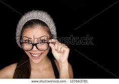 Cool hipster student woman wearing eyewear glasses and knit hat isolated on black background Multiracial mixed race Asian Chinese / Caucasian female university student looking at camera smiling happy. - stock photo