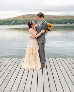 Bride and groom on jetty at Finger Lakes © Sarah Tew Photography http://www.sarahtewphotography.com  as featured on The Wedding Community Venue: Fontainebleau Inn, New York / Bride's Dress: Leanne Marshall / Bride's Shoes: Christian Louboutin / Hair Piece: Twigs & Honey / Bridal Jewelery: Tiffany & Co. / Hair and Make-Up: Miel Beauty / Groom's Suit: Michael Andrews Bespoke / Flowers: Plenty of Posies / Catering: Dano's / Wedding Cake: Daphne Nolder / Invitations: Tony Tino / Placecards…