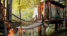 This whimsical treehouse is made of reclaimed materials, has a hanging bridge connecting the two spaces, operable hopper-style windows and hanging string lights for added magic.
