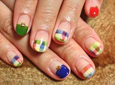 Multi colored gingham designed French tips. Gold beads are placed on top of the French tip design along with a combination of blue, green, white and melon colors.