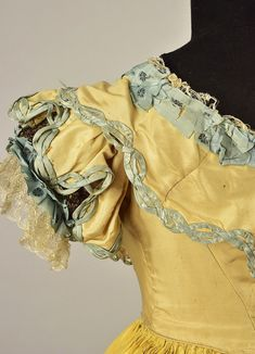 TRAINED SILK BALLGOWN, attributed to JULIA GARDINER, c. 1852 Tan 2-piece having back-lacing bodice with deep front and back points, and short puffed sleeve, decorated with blue ribbon, lace and metallic gold thread, bodice and skirt center panel embroidered in blue and cream silk floral, the skirt having a series of scalloped ruffles, set in yellow silk appliquéd with a polychrome floral on pink set within blue braided wreaths with bows, tan scalloped hem ruffle.