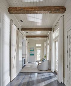 Floor to ceiling shiplap paneling with reclaimed wood beam. This hallway boasts rustic wood beam ceiling, shiplap walls, shiplap ceiling as well a wall of French doors and transom windows dressed in white cotton curtains. Shiplap Paneling, Shiplap Ceiling, Ceiling Beams, Hallway Ceiling, Plank Ceiling, Exposed Basement Ceiling, Shiplap Wood, White Ceiling, Wood Ceilings
