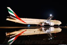 Airliners.net - Gorgeous reflection in the water at night of an Emirates B777-31H/ER Getting ready for its flight back to Dubai.