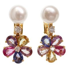 These stunning earrings from Bvlgari's Color collection feature 5-petal flower-shaped drops set with natural multi-color faceted pear-cut sapphires and a pair of sparkling solitaire diamonds. Completed with 10.0mm Keshi Cultured Pearls. Chic and fabulous. 21st century