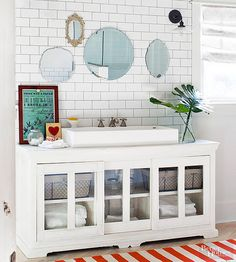 A long media cabinet becomes the perfect base for a trough sink while providing plenty of additional counter space. Glass-front sliding doors on this DIY bathroom vanity make for grab-and-go storage with style.