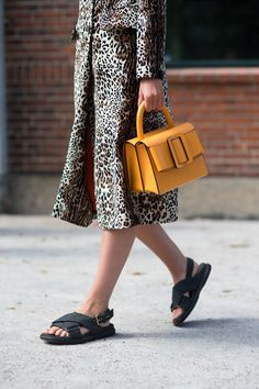 A model at SS17 Copenhagen Fashion Week wears a leopard print coat and accessorises with an ochre-yellow handbag and flat sandals