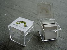 "Inchie Box $1.59 It is a 1.25"" clear acrylic cube with hinged lid & Inchie Arts logo on top.The Box holds about 12 to 20 Inchie Squares depending on whether they are flat or 3D."