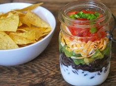 This simple layered dip is beautiful! It will be a crowd favorite if served at parties! The taste and the beauty. Why does food look so much better in a mason jar?!? 30 Mason Jar Foods and Recipe Ideas | via putitinajar.com