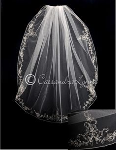 A flowery, silver embroidered vine pattern adorned with beads accents the edge of this fingertip bridal veil with an embroidered edge. It is fingertip length, 40 inches long and 72 inches wide, on a f