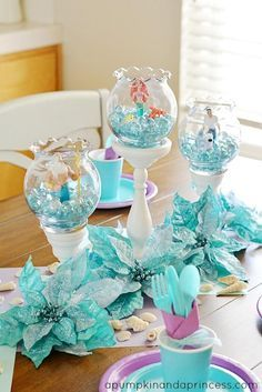 DIY Little Mermaid Table scape. Centerpieces can be made from Dollar Store items: Fish bowl vases Candle Sticks (painted) Silk Flowers (or left over Christmas Poinsettias) Glass Beads Little Mermaid figurines Too cute for a Mermaid or Under the Sea themed party!