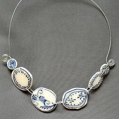 "https://flic.kr/p/6sxd2N | Swirl fleur porcelain necklace | Fleurs Necklace 8"" x 10"" (approx.) $200 Loose and whimsical, the decoration on these handmade porcelain shapes is applied using a slip-trailer. The process creates a slightly raised line that adds texture to the piece. Glazed with a clear glaze, connected with handmade metal links, and finished with a dark blue ribbon, each necklace is an original composition."