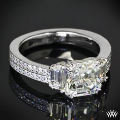 This beautiful diamond engagement ring is adorned with 0.45ctw A CUT ABOVE ® Hearts and Arrows Diamond Melee. The 2.06ct Asscher center stone is flanked by two Trapezoid side stones.