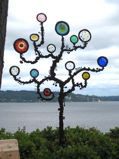 cool yard tree sculpture with glass rondels by Myorian Studio  What a great creative idea. of course the borrowed view doesn't hurt either..Makes the sculpture stand out!